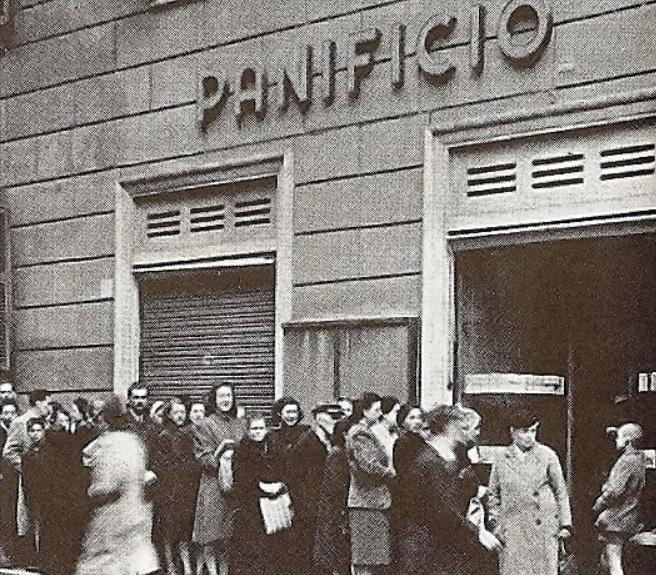 Donne e uomini in coda davanti a una panetteria. Il pane è razionato, fatto di farine miste; si ottiene con un tagliando della tessera annonaria, ma spesso non si trova