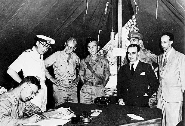 Il generale Castellano, in borghese, è il secondo da destra; il primo (che non appare nelle fotografie generalmente riprodotte perché ritagliate) è l'interprete, cioè il diplomatico Franco Montanari, da qualcuno scambiato per l'avvocato Vito Guarrasi