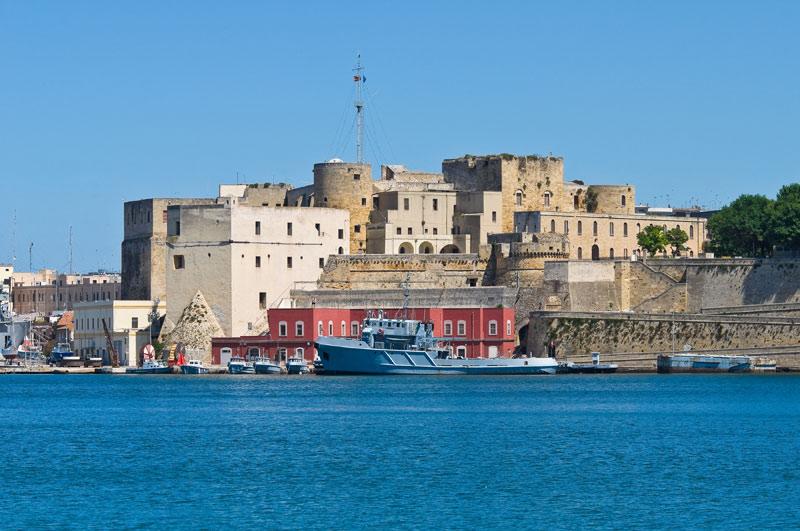 Il castello svevo visto dal porto interno. Di origini normanne, è stato trasformato nel Trecento ed è un impianto a più volumi. Nei locali al primo piano, sede dell'ammiragliato, hanno trovato ospitalità il re Vittorio Emanuele e la regina Elena